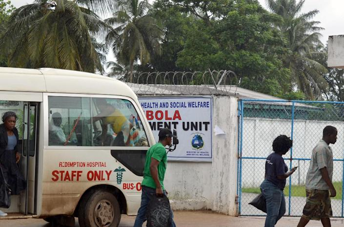 People walk on October 11, 2014 outside the Ebola Island Clinic in Monrovia (AFP Photo/Zoom Dosso)
