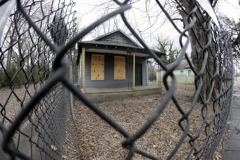 FILE - In this Jan. 16, 2017, file photo, the abandoned childhood home of singer Aretha Franklin sits behind a security fence in Memphis, Tenn. Recently, the Franklin birthplace and the surrounding neighborhoods have moved to the forefront of a large cleanup effort, as the city refuses to accept decay as a fact of life in the urban landscape. (AP Photo/Mark Humphrey, File)