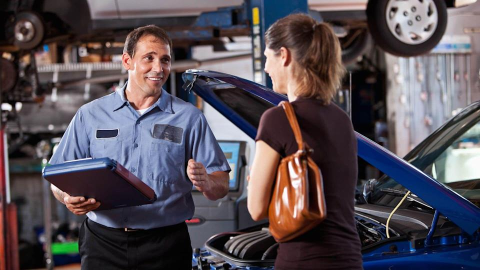 Auto mechanic  with female customer discussing car repairs.