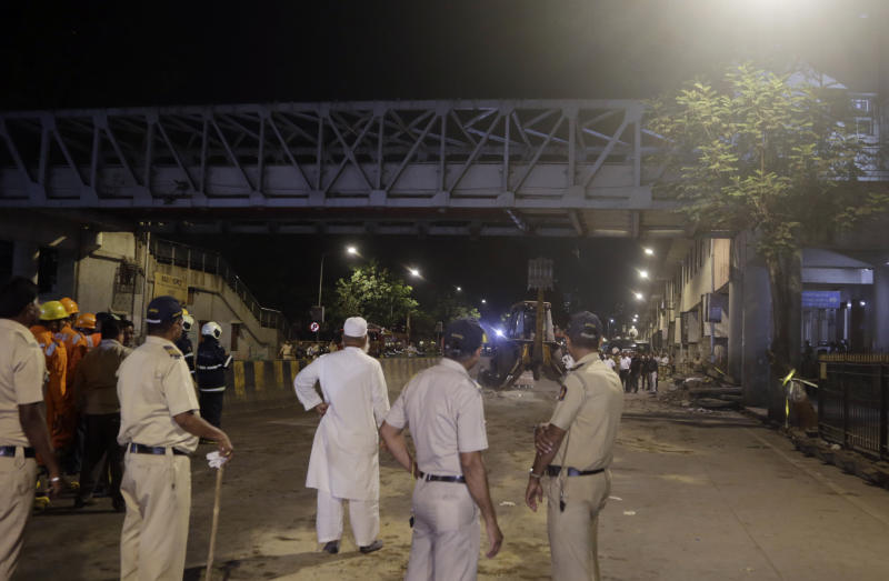 Policemen look at a pedestrian bridge after a part of it collapsed in Mumbai, India, Thursday, March 14, 2019. A pedestrian bridge connecting a train station with a road collapsed in Mumbai on Thursday, killing at least five people and injuring more than 30, police said. (AP Photo/Rajanish Kakade)