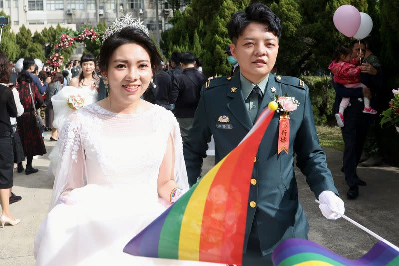 Chen Ying-Hsuan, a combat engineer lieutenant, and her wife Li Chen-Chen, are seen during a military mass wedding in Taoyuan