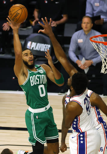 Jayson Tatum, left, of the Boston Celtics shoots against Joel Embiid, right, of the Philadelphia 76ers during the first half of Game 2 of an NBA basketball first-round playoff series, Wednesday, Aug. 19, 2020, in Lake Buena Vista, Fla. (Kevin C. Cox/Pool Photo via AP)
