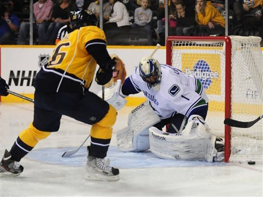 Vancouver Canucks goalie Roberto Luongo (1) watches the puck as Nashville Predators left wing Rich Clune (16) approaches in the second period of an NHL hockey game on Friday, Feb. 22, 2013, in Nashville, Tenn. Luongo made 23 saves for the shutout and the Canucks 1-0 win against the Predators. (AP Photo/Mike Strasinger)