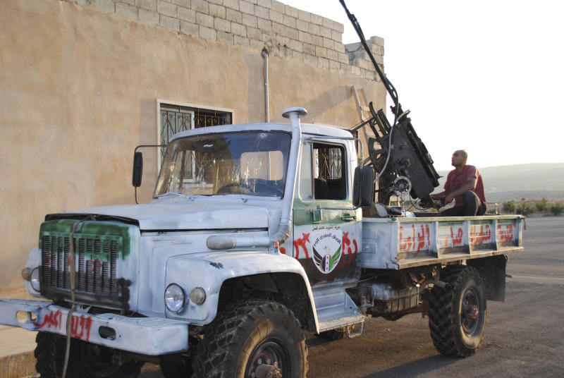 In this Tuesday, July 24, 2012 photo, a Syrian rebel sits in the back of truck mounted with an anti aircraft weapon during clashes with Syrian troops in Idlib, Syria. (AP Photo/Fadi Zaidan)