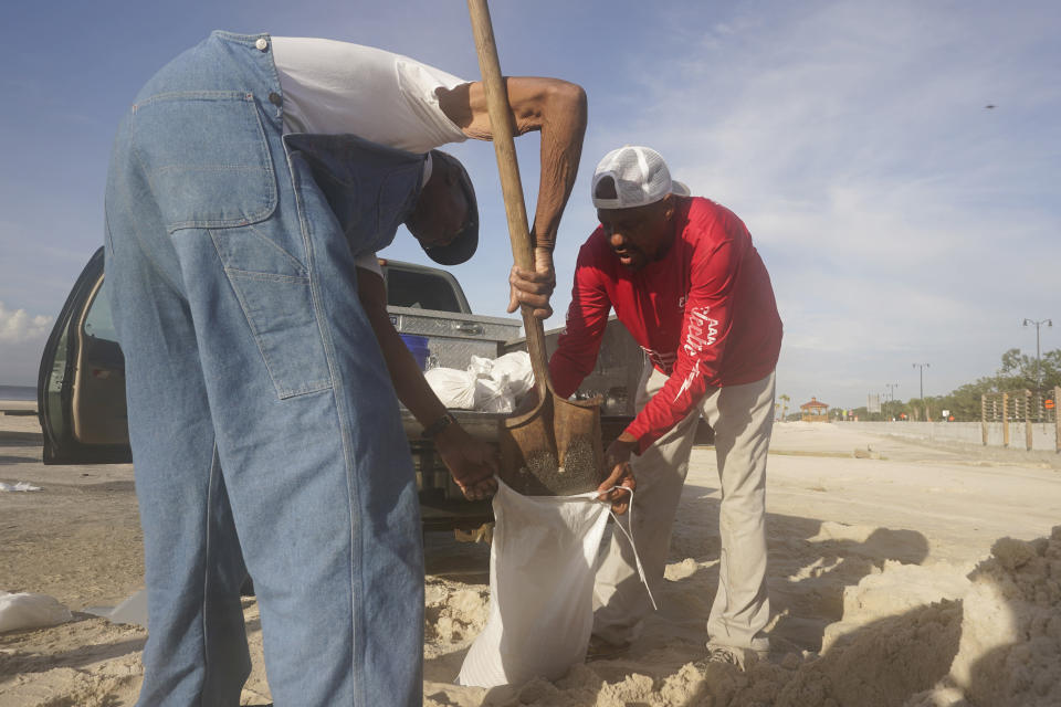 Gregory Moore, right, helps a local residents fill sand bags as they prepare for the expectd arrival of Hurricane Ida Saturday, Aug. 28, 2021, in Gulfport, Miss. (AP Photo/Steve Helber)