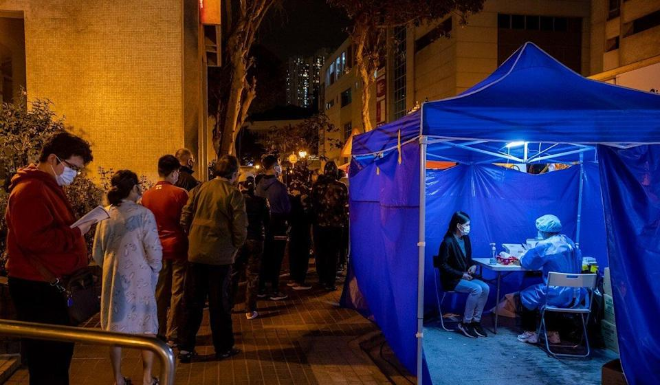 Residents queue up for Covid-19 tests outside a building under lockdown at Laguna City residential estate on Sunday night. Photo: Bloomberg
