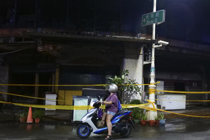 A woman looks passes a building after a fire, in Kaohsiung, southern Taiwan, Thursday, Oct. 14, 2021. Officials say at least 46 people were killed and over 40 injured after a fire broke out in a decades-old mixed commercial and residential building in the Taiwanese port city of Kaohsiunging. Neighborhood residents say the 13-story building was home to many poor, elderly and disabled people and it wasn't clear how many of the 120 units were occupied. (AP Photo/Huizhong Wu)