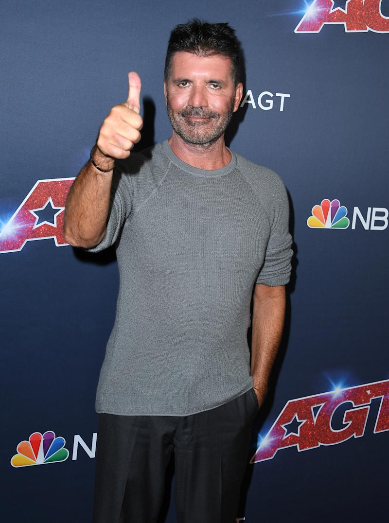 A very slim Simon flashed a thumbs up to cameras at the event. Photo: Getty Images