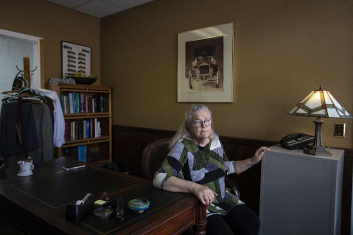 Georgia DeFilippo, wife of Frank Carson, sits at a desk in his office.