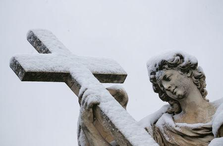 A statue is seen covered in snow during a heavy snowfall in Rome. REUTERS/Alessandro Bianchi