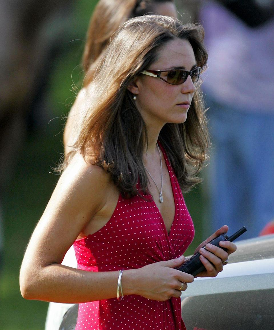 <p>Carrying a police radio as she watches Prince William compete in the Chakravarty Cup charity polo match at Ham Polo Club in Richmond, England.</p>