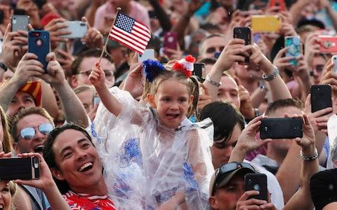 "A child waves flags as people take photos while U.S. President Donald Trump and first lady Melania Trump arrive for the ""Salute to America"" event  - Credit: Reuters"