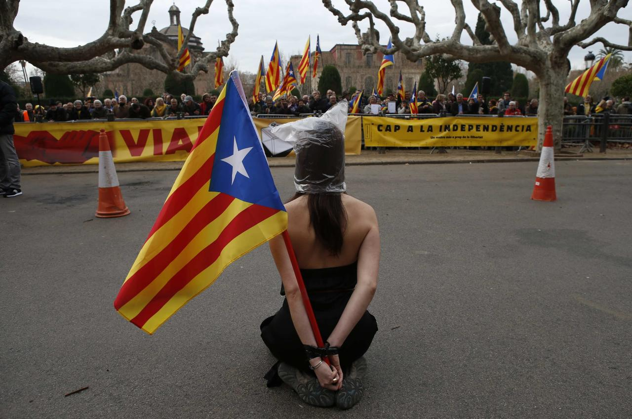 A pro-independence protestor sits in front of other demonstrators next to Catalonia's regional parliament as lawmakers voted inside, in Barcelona, January 16, 2014. Local lawmakers in the northeastern Spanish region of Catalonia voted to seek a referendum on breaking away from Spain on Thursday, setting themselves up for a battle with an implacably opposed central government in Madrid. The Catalan Parliament in Barcelona voted 87 to 43, with 3 abstentions, to send a petition to the national parliament seeking the power to call a popular vote on the region's future. The independence movement in Catalonia, which has its own language and represents a fifth of Spain's national economy, is a direct challenge to Prime Minister Mariano Rajoy, who has pledged to block a referendum on constitutional grounds. REUTERS/Albert Gea (SPAIN - Tags: POLITICS CIVIL UNREST)