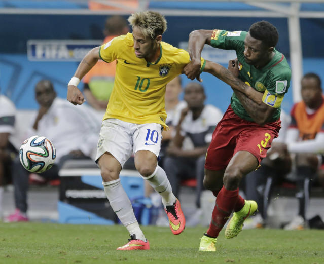 Cameroon's Nicolas N'Koulou holds Brazil's Neymar during the group A World Cup soccer match between Cameroon and Brazil at the Estadio Nacional in Brasilia, Brazil, Monday, June 23, 2014. (AP Photo/Bernat Armangue)