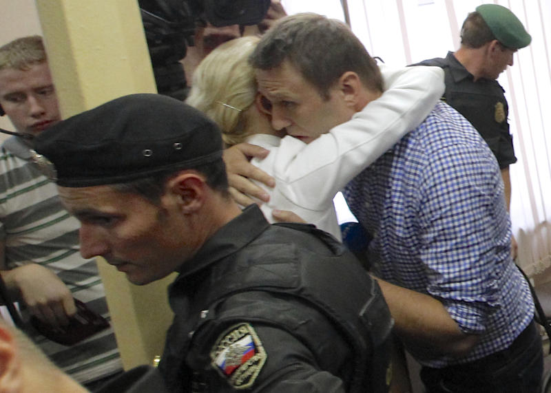 Russian opposition leader Alexei Navalny, embraces his wife Yulia at a court in Kirov, Russia Thursday, July 18, 2013. Alexei Navalny, one of the Russian opposition's leading figures, was convicted of embezzlement Thursday and sentenced to five years in prison. (AP Photo/Dmitry Lovetsky)
