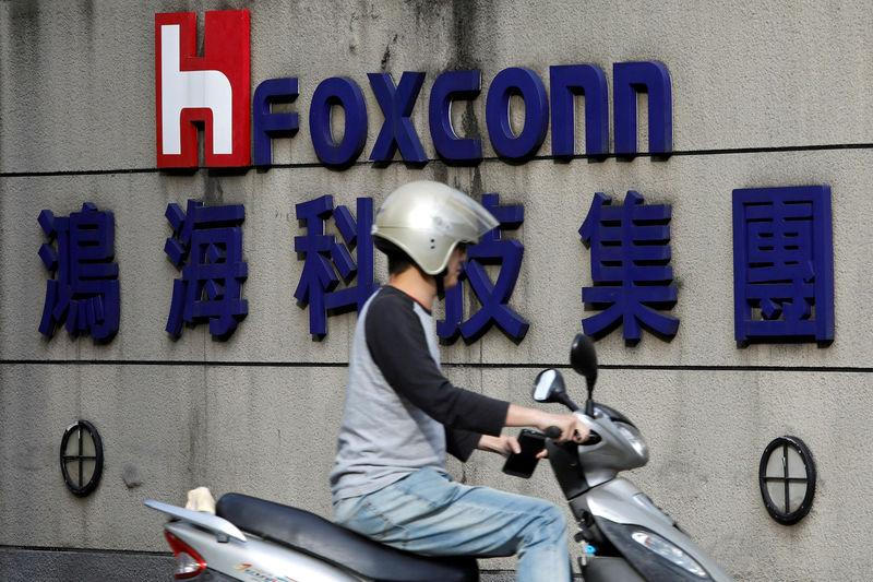 FILE PHOTO: A motorcyclist rides past the logo of Foxconn, the trading name of Hon Hai Precision Industry, in Taipei