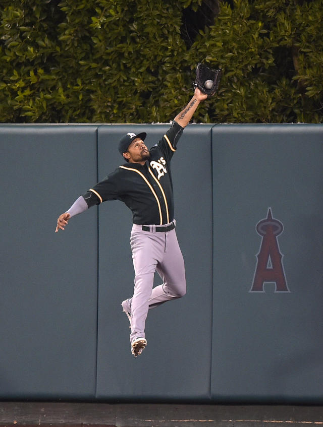 A's center fielder Coco Crisp robs Mike Trout of a hit in the third inning Monday night. (AP Photo)