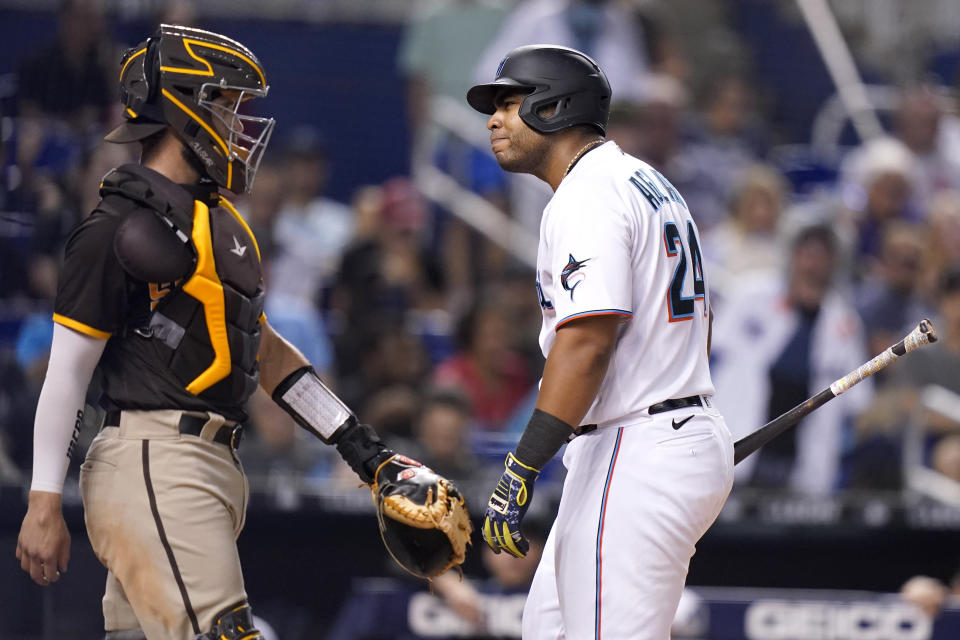 Miami Marlins' Jesus Aguilar, right, reacts after striking out during the fourth inning of a baseball game, next to San Diego Padre catcher Austin Nola on Thursday, July 22, 2021, in Miami. (AP Photo/Lynne Sladky)