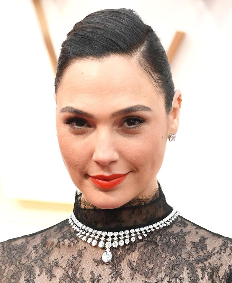 <p>The Wonderwoman actress opted for an orange/red lip and slick side swept bun for the Oscars.</p>