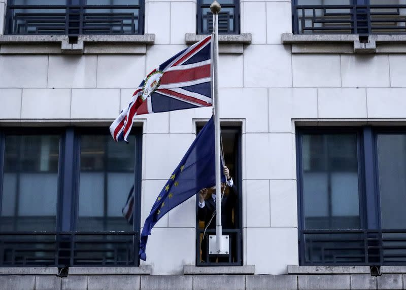 An official removes the EU flag from Britain's Permanent Representation to the EU in Brussels
