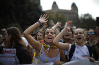People, some wearing yellow ribbons in support of jailed pro-independence politicians, protest in Barcelona, Spain, Monday, Oct. 14, 2019. Spain's Supreme Court on Monday convicted 12 former Catalan politicians and activists for their roles in a secession bid in 2017, a ruling that immediately inflamed independence supporters in the wealthy northeastern region. Poster reads in Catalan, General Strike. (AP Photo/Emilio Morenatti)