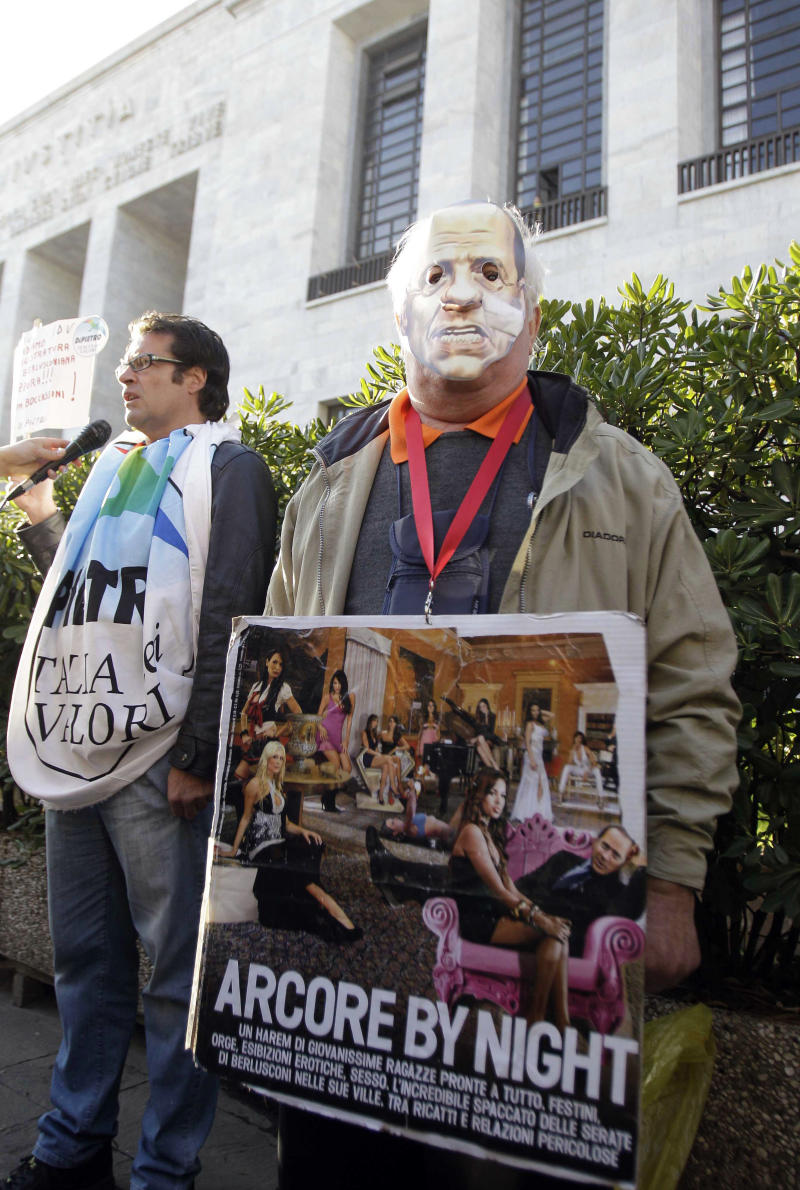 """A man wearing a mask of Italian Premier Silvio Berlusconi holds a placard reading """"Arcore by night"""", a reference to Berlusconi's villa in the village of Arcore, near Milan, where he allegedly hosted parties, during a protest outside the Milan court, Italy, Wednesday, April 6, 2011. The trial of Premier Silvio Berlusconi on charges he paid for sex with an underage prostitute, then tried to use his influence to cover it up was adjourned shortly after it opened in Milan on Wednesday. Berlusconi did not attend the hearing, which lasted seven minutes and was devoted to formalities. The trial was adjourned to May 31. (AP Photo/Luca Bruno)"""