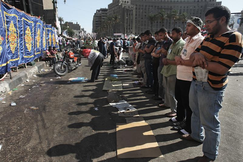 Egyptians pray in Tahrir Square, Cairo, Egypt, Thursday, June 21, 2012. Authorities delayed Thursday's planned announcement of the winner of Egypt's presidential election, likely for several days hiking tension as allegations of fraud swirled as each candidate declared he was the victor. Hundreds of Brotherhood supporters camped out in Cairo's Tahrir Square on Wednesday night, denouncing the ruling military and vowing to stay in place until the parliament, which was dissolved last week on a court order, is reinstated. (AP Photo/Mohammed Abu Zaid)
