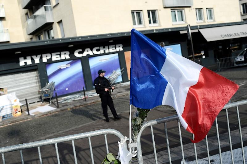 A French policeman stands guard outside the Hyper Cacher shop, where gunmen took hostages on January 9, 2015 in Paris