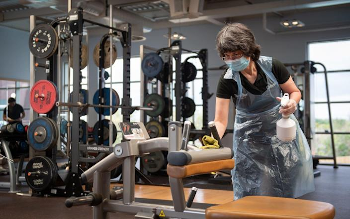 A member of staff cleans down gym equipment at David Lloyd in Cambridge - Joe Giddens/PA Wire