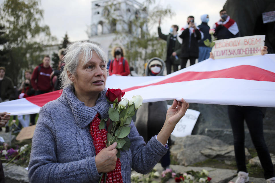 A woman holds red and white roses and an old Belarusian national flags during an opposition rally to protest the official presidential election results in Minsk, Russia, Monday, Oct. 26, 2020. Factory workers, students and business owners in Belarus have started a general strike, calling for authoritarian President Alexander Lukashenko to resign after more than two months of mass protests triggered by a disputed election. (AP Photo)