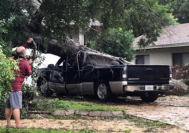<p>An unidentified man looks at a truck that was crushed by a falling tree in Fort Walton Beach, Florida on June 21, 2017. (Photo: Tom Mclaughlin/Northwest Florida Daily News via AP) </p>