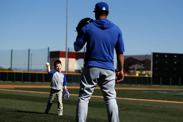 Chicago Cubs catcher Willson Contreras, right, plays catch with fan Ivan Weinhold during spring training baseball Wednesday, Feb. 12, 2020, in Mesa, Ariz. (AP Photo/Gregory Bull)