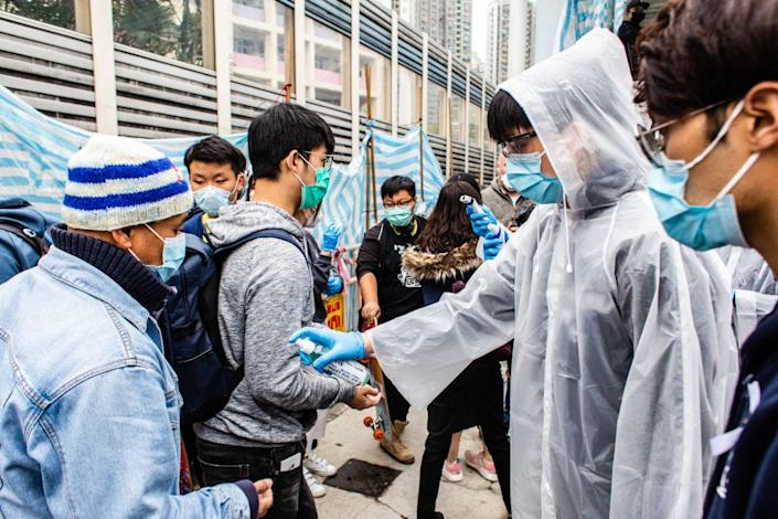 <br>A volunteer offers hand sanitizer to passengers who recently arrived in Hong Kong from mainland China on February 4.