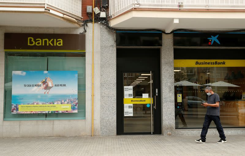 A man walks past branches of Bankia and Caixabank in Barcelona
