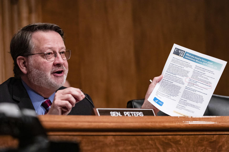 Sen. Gary Peters, D-Mich., holds a leaflet from the Centers for Disease Control and Prevention on COVID-19 during a Senate Homeland Security Committee hearing on March 5. (Samuel Corum/Getty Images)