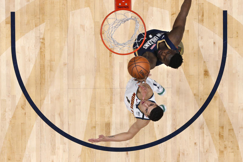 New Orleans Pelicans forward Zion Williamson, top, battles for a rebound against Denver Nuggets forward Michael Porter Jr. (1) in the second half of an NBA basketball game in New Orleans, Friday, Jan. 24, 2020. (AP Photo/Gerald Herbert)