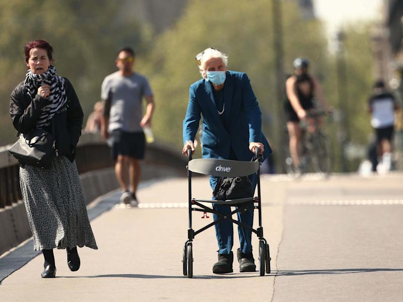 An elderly woman wearing a face mask and using a walker on Westminster Bridge, London, during the coronavirus lockdown: Yui Mok/PA