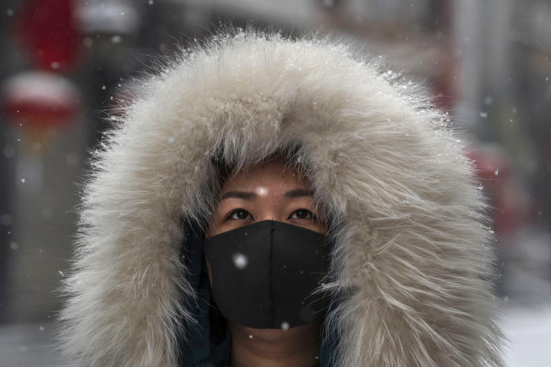 BEIJING, CHINA - FEBRUARY 05: A Chinese woman wears a protective mask as she walks during a snowfall in an empty and shuttered commercial street on February 5, 2020 in Beijing, China. China's stock markets tumbled in trading on Monday, the first day back after an extended Lunar New Year holiday as a mystery virus continues to spread in China and worldwide. The number of cases of a deadly new coronavirus rose to more than 20000 in mainland China Wednesday, days after the World Health Organization (WHO) declared the outbreak a global public health emergency. China continued to lock down the city of Wuhan in an effort to contain the spread of the pneumonia-like disease which medicals experts have confirmed can be passed from human to human. In an unprecedented move, Chinese authorities have put travel restrictions on the city which is the epicentre of the virus and neighbouring municipalities affecting tens of millions of people. The number of those who have died from the virus in China climbed to over 490 on Thursday, mostly in Hubei province, and cases have been reported in other countries including the United States, Canada, Australia, Japan, South Korea, India, the United Kingdom, Germany, France and several others. The World Health Organization has warned all governments to be on alert and screening has been stepped up at airports around the world. Some countries, including the United States, have put restrictions on Chinese travellers entering and advised their citizens against travel to China. (Photo by Kevin Frayer/Getty Images)