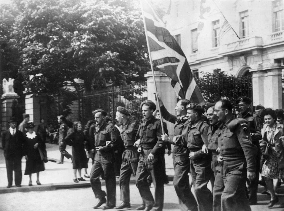 <p>British soldiers celebrate their victory—and the fact that they'll be returning home soon—by waving a British flag in the streets of Paris. </p>