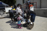 Haitian migrants deported from the US gather after their arrival to the Toussaint Louverture International Airport in Port-au-Prince, Haiti, Sunday, Sept. 19, 2021. Thousands of Haitian migrants have been arriving to Del Rio, Texas, to ask for asylum in the U.S., as authorities begin to deported them to back to Haiti. (AP Photo/Rodrigo Abd)