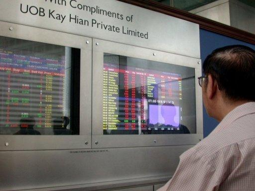 An elderly investor monitors share prices at a bank in Singapore. (AFP)