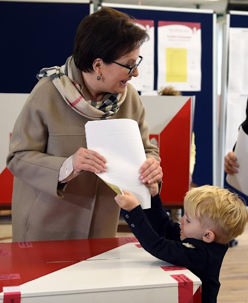 Incumbent Prime Minister Ewa Kopacz, leader of Poland's liberal-leaning Civic Platform party (PO), gets an assist from grandson Julian as she casts her ballot October 25, 2015 in Warsaw (AFP Photo/Janek Skarzynski)