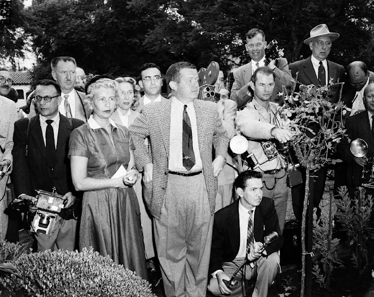 In this Oct. 6, 1954 file photo, Associated Press reporter Bob Thomas, center, and other media wait outside the Beverly Hills house of Marilyn Monroe, after reports that the movie star's marriage to baseball star Joe DiMaggio was breaking up. Thomas, the longtime Associated Press reporter who kept the world informed on the comings and goings of Hollywood's biggest stars, died of age-related illnesses Friday, March 14, 2014 at his Encino, Calif., home, his daughter Janet Thomas said. He was 92. (AP Photo)