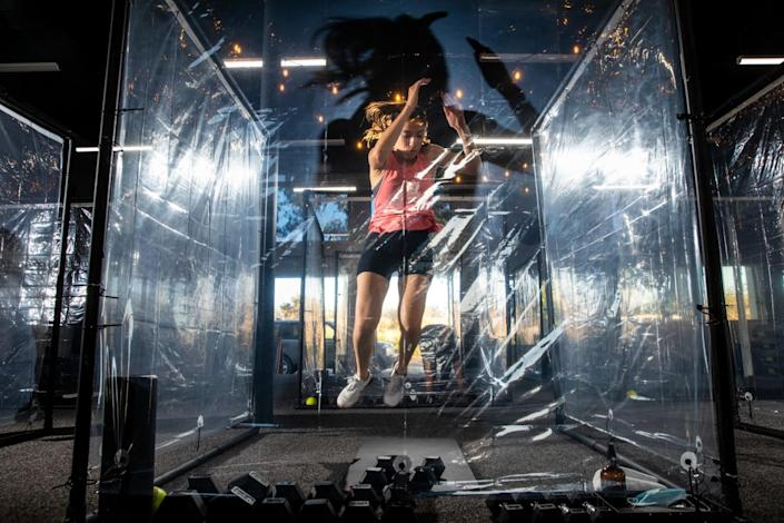 A woman jumps while exercising inside a transparent plastic pod in a gym
