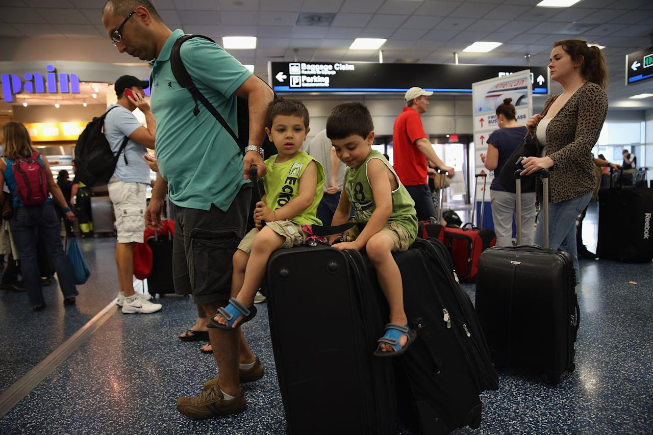 MIAMI, FL - APRIL 16:  American Airlines passengers Khalid Saadah, pulls his son's, Yousef Saadah (C) and Mohammad Saadah on their luggage as they wait in line to get their tickets at Miami International Airport on April 16, 2013 in Miami, Florida. Thousands of American Airlines travelers became stranded today when the airline was forced to ground all its flights after a nationwide problem with its computer systems  (Photo by Joe Raedle/Getty Images)