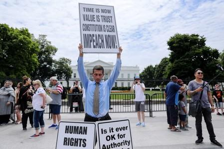 "Steve Swanson protests in silence with a sign over his head reading ""Impeach Now!"" in front of the White House in Washington"