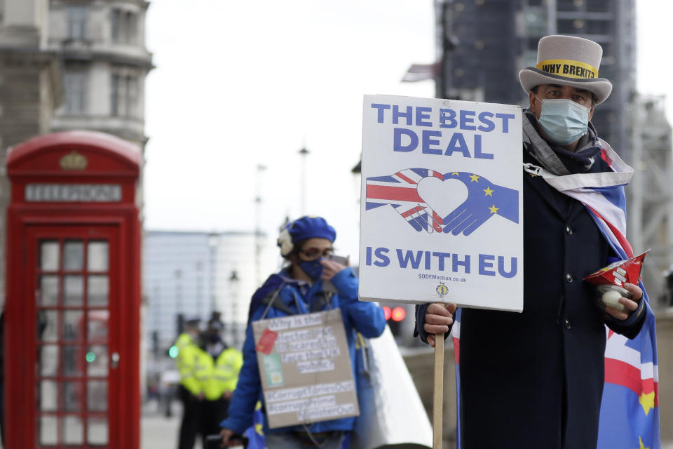"""Steve Bray, right, a pro EU campaigner during a protest against a Brexit no deal near Parliament in London, Wednesday, Nov. 25, 2020. The European Union has committed to be """"creative"""" in the final stages of the Brexit trade negotiations but warned that whatever deal emerges, the United Kingdom will be reduced to """"just a valued partner,"""" far removed from its former membership status. (AP Photo/Kirsty Wigglesworth)"""