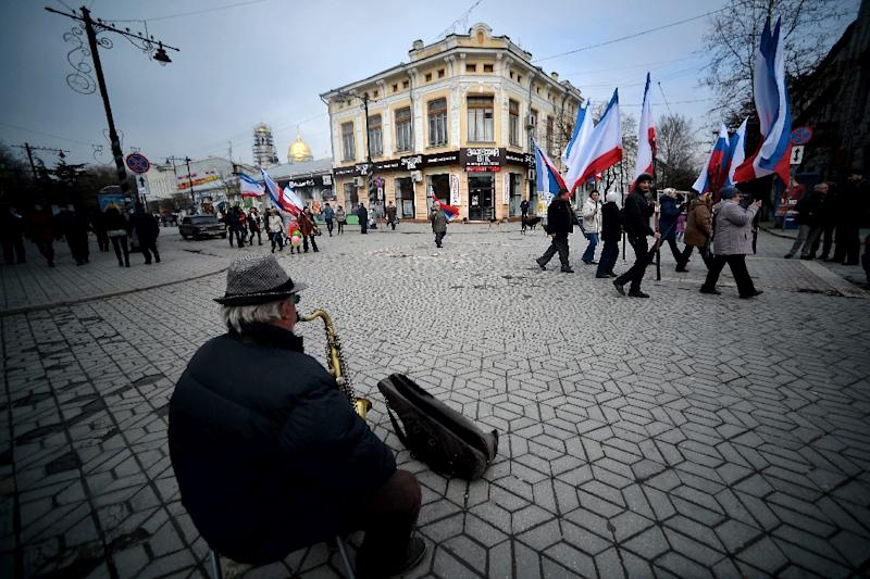 A file picture taken on March 9, 2014 shows a man playing a saxopone as people waving Russian and Crimean flags walk to a pro-Russia rally in Simferopol's Lenin Square (AFP Photo/Filippo Monteforte)