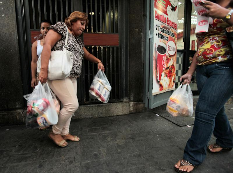 FILE - In this May 15, 2013 file photo, a customer leaves a private super market with her purchases, including toilet paper, in Caracas, Venezuela.  In June of 2013, Venezuela's state of Zulia on the border with Colombia will begin restricting the sale of 20 basic items, including toilet paper and chicken, that are subject to price controls. (AP Photo/Fernando Llano, File)