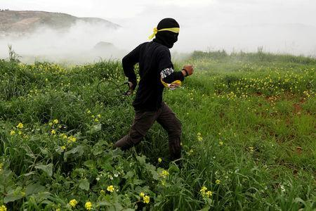 A Palestinian demonstrator runs from tear gas fired by Israeli troops during a protest marking the Land Day in al-Mughayer village, in the Israeli-occupied West Bank March 29, 2019. REUTERS/Mohamad Torokman